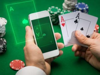 Två händer som håller i en mobiltelefon och två spelkort på ett spelbord fullt av spelmarker.